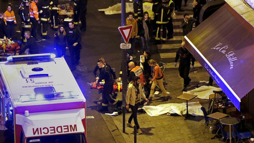 Le personnel des services de secours travaille à l'extérieur du restaurant Le Carillon après la fusillade à Paris le 13 novembre 2015.